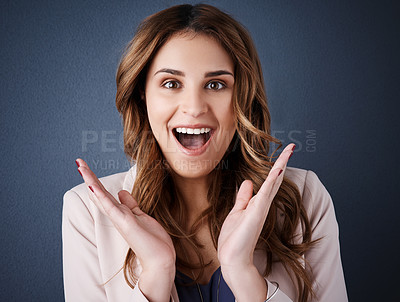 Buy stock photo Studio portrait of an attractive young businesswoman looking surprised against a dark blue background