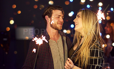 Buy stock photo Cropped shot of an attractive young couple having fun with sparklers at a nightclub