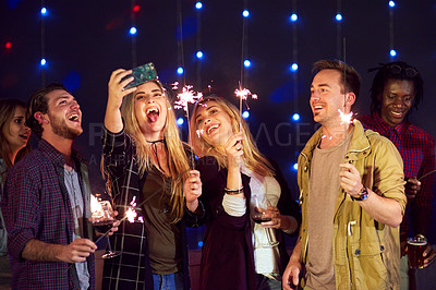 Buy stock photo Cropped shot of a group of friends taking a selfie while having fun at a nightclub