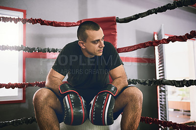 Buy stock photo Shot of a confident young male boxer seated in the corner of a boxing ring at a gym during the day