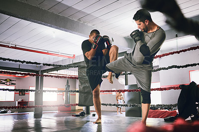Buy stock photo Shot of two young male boxers facing each other in a training sparing match inside of a boxing ring at a gym during the day