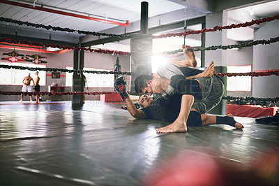 Buy stock photo Shot of two young male boxers facing each other in a training sparing match inside of a boxing ring on the floor at a gym during the day