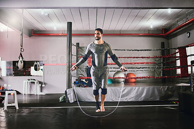 Buy stock photo Shot of a focused young male boxer using a skipping rope for training exercises inside of a gym during the day
