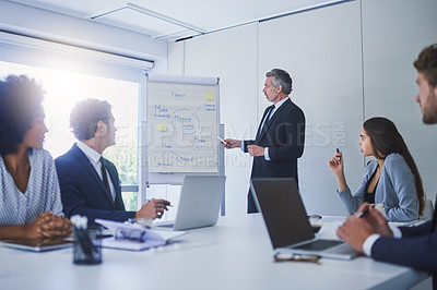 Buy stock photo Shot of a mature businessman giving a presentation to his colleagues in an office