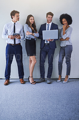 Buy stock photo Shot of a diverse group of businesspeople using wireless technology while standing against a grey background