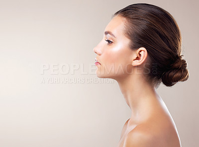 Buy stock photo Studio profile of a beautiful young woman posing against a beige background