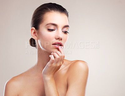 Buy stock photo Studio shot of a beautiful young woman posing against a beige background