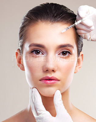 Buy stock photo Studio portrait of a beautiful young woman getting her face injected by gloved hands against a beige background