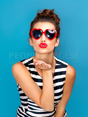 Buy stock photo Studio shot of a beautiful young woman wearing sunglasses while posing against a blue background