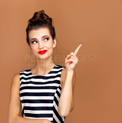 Buy stock photo Studio shot of a beautiful young woman pointing to copyspace against a bronze background