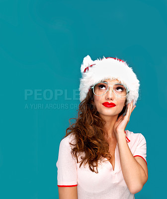 Buy stock photo Studio shot of a beautiful young woman wearing a Christmas hat against a turquoise background
