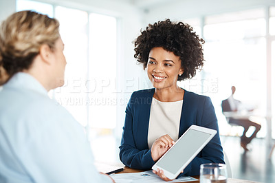 Buy stock photo Shot of two young businesswomen using a digital tablet during a discussion in a modern office