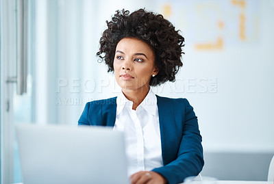 Buy stock photo Shot of a young businesswoman using a laptop at her desk in a modern office and looking thoughtful