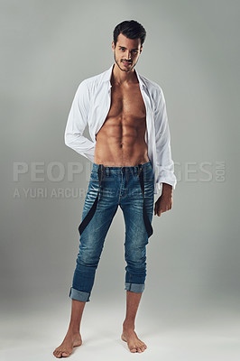 Buy stock photo Studio shot of a handsome young man wearing jeans and a white shirt against a grey background