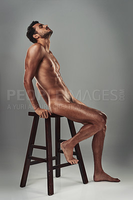 Buy stock photo Studio shot of a handsome young man sitting on a chair in the nude against a grey background