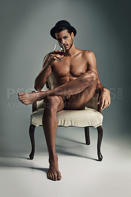 Buy stock photo Studio shot of a handsome and muscular young man having a drink in the nude against a grey background