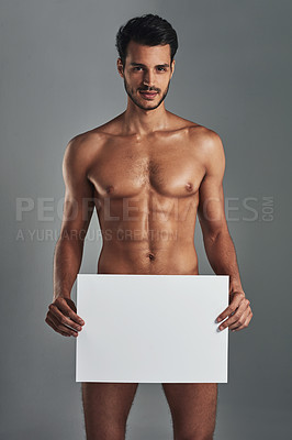 Buy stock photo Studio shot of a handsome and muscular young man holding a blank sign against a grey background
