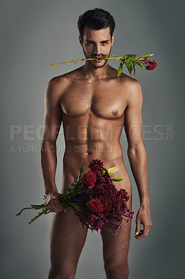 Buy stock photo Studio shot of a handsome young man holding a bunch of roses in the nude against a grey background