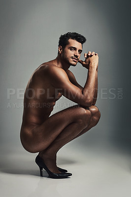 Buy stock photo Studio shot of a handsome and muscular young man wearing high heels in the nude against a grey background