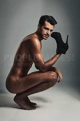 Buy stock photo Studio shot of a handsome and muscular young man holding stilettos in the nude against a grey background