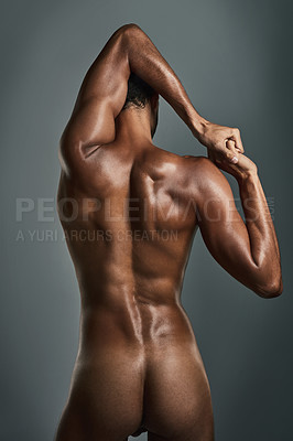 Buy stock photo Rearview studio shot of a muscular young man posing against a grey background