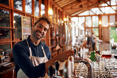 Buy stock photo Portrait of a cheerful young barman pouring a glass of beer inside of a beer brewery during the day
