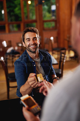 Buy stock photo Shot of a cheerful young man making a payment to a barman through use of a credit card inside a beer brewery during the day