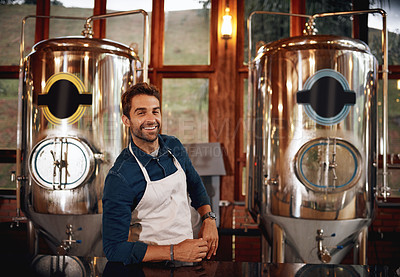 Buy stock photo Portrait of a cheerful young barman leaning on the bar counter waiting for customers to serve inside of a beer brewery