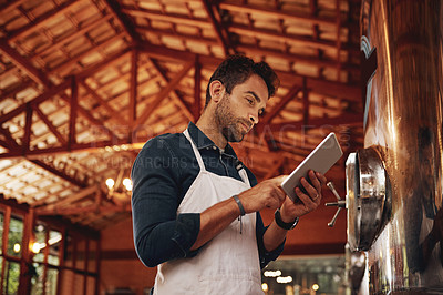 Buy stock photo Shot of a cheerful young barman browsing on a digital tablet while keeping track of stock inside of a beer brewery during the day