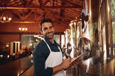 Buy stock photo Portrait of a cheerful young barman browsing on a digital tablet while keeping track of stock inside of a beer brewery during the day