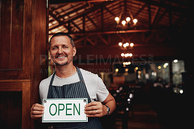 Buy stock photo Portrait of a cheerful middle aged business owner holding up a sign saying