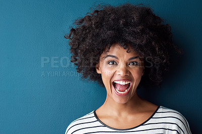 Buy stock photo Studio portrait of an attractive young woman looking surprised against a blue background