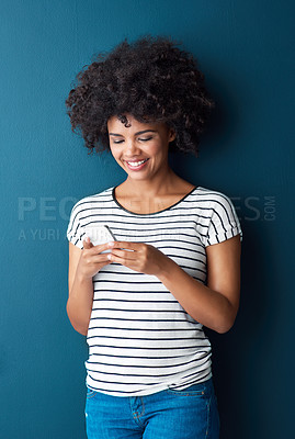 Buy stock photo Studio shot of an attractive young woman using a cellphone against a blue background