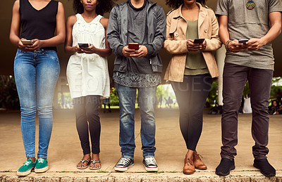 Buy stock photo Cropped shot of a group of unrecognizable people using cellphones in a public park