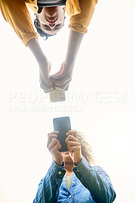 Buy stock photo Low angle shot of beautiful women using cellphones in a public park