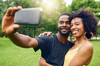 Buy stock photo Cropped shot of an affectionate young couple taking selfies while spending some time in the park