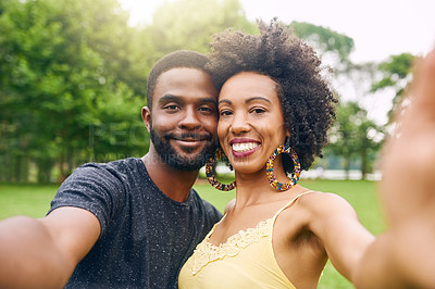 Buy stock photo Cropped portrait of an affectionate young couple taking selfies while spending some time in the park