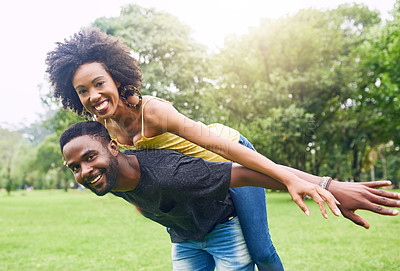 Buy stock photo Cropped portrait of a handsome young man piggybacking his girlfriend around the park