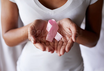 Buy stock photo Cropped shot of a woman holding a pink breast cancer awareness ribbon