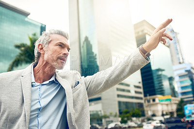Buy stock photo Shot of a mature businessman gesturing to get a cab in the city