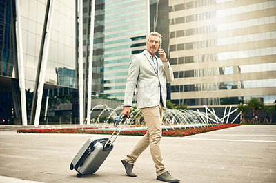 Buy stock photo Shot of a mature businessman talking on a cellphone while walking with a suitcase in the city