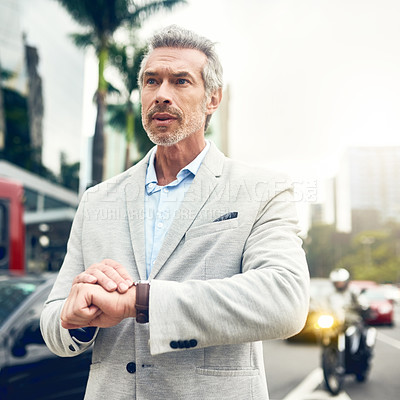Buy stock photo Shot of a mature businessman checking the time on his wrist watch out in the city