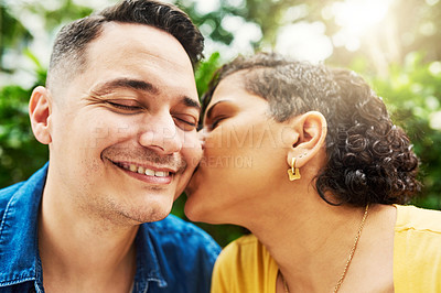 Buy stock photo Cropped shot of a young woman kissing her husband on the cheek while in the park