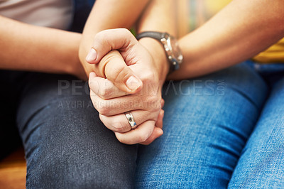 Buy stock photo Cropped shot of an unrecognizable couple holding hands tightly while sitting in the park