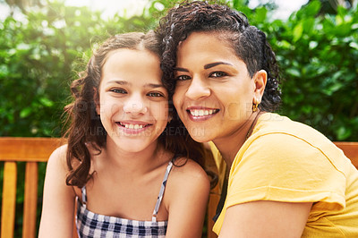 Buy stock photo Cropped portrait of a young woman and her adorable little girl sitting on a bench in the park