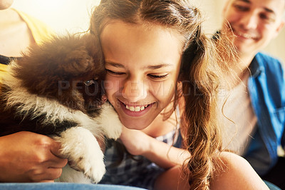 Buy stock photo Cropped shot of an adorable little girl cuddling with her puppy while sitting on the sofa at home with dad