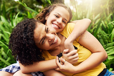 Buy stock photo Cropped portrait of an adorable young girl and her mother embracing in the park