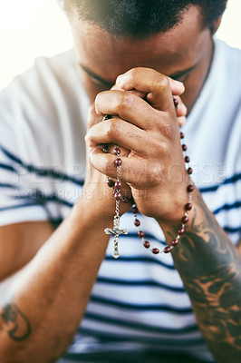 Buy stock photo Cropped shot of a young man holding his rosary while praying