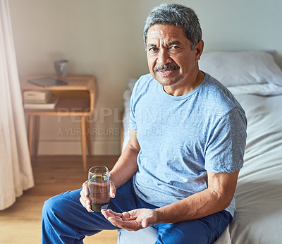 Buy stock photo Portrait of a cheerful mature man seated on his bed and about to drink medication with water in the bedroom at home during the day