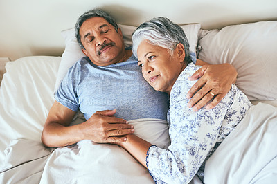 Buy stock photo Shot of a relaxed mature couple lying in bed together at home in during the morning hours